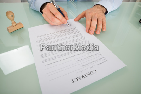 person hand signing contract form