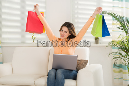 woman holding multi colored shopping bag