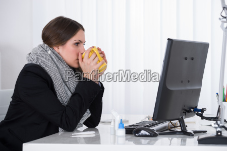 businesswoman drinking with mug at desk