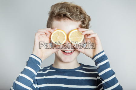 smiling boy holding slices of lemons