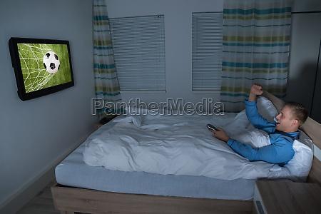 man beobachtet fussball match im fernsehen