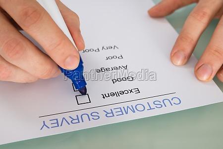 person hand marking on customer survey