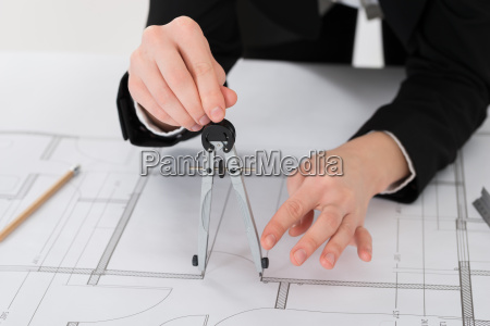 female architect hands holding compass on