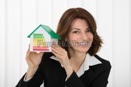 businesswoman holding house model with energy