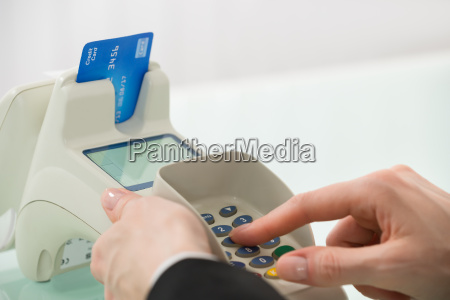 woman pressing button on credit card