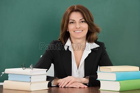 weiblicher lehrer sitzt am klassenzimmer
