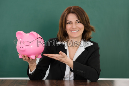 female teacher holding piggybank