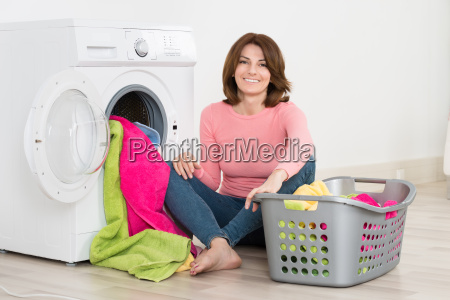 happy woman putting clothes into washing