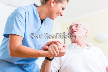 senior nurse holding hand from senior