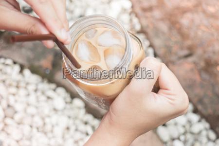hand auf glas eismilchkaffee mit vintage