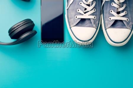 kopfhoerer smartphone und turnschuhe