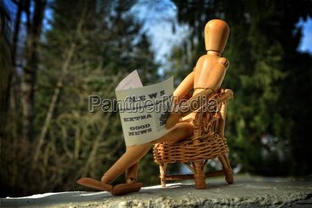 holzfigur sitzt auf terasse im sessel