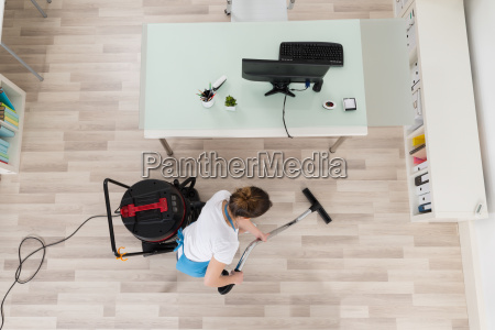 female janitor cleaning wooden floor with