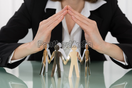 woman hand protecting cut out figures