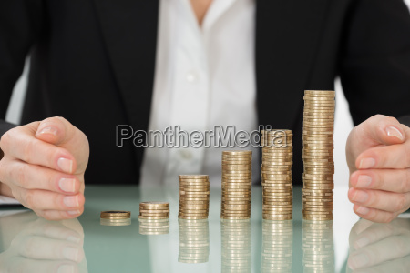 businesswoman protecting stacked coins on desk