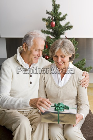 senior couple exchanging christmas presents at