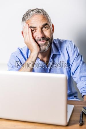 potrait des laechelnden geschaeftsmannes mit laptop