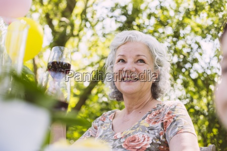 smiling senior woman holding glass of
