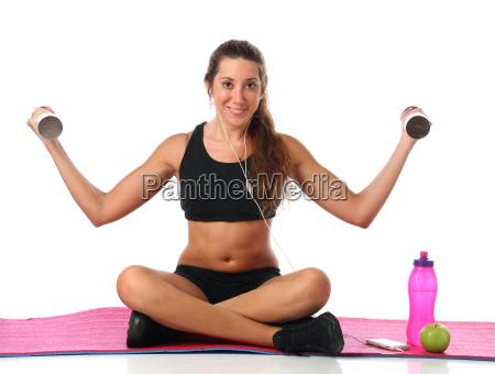 glueckliche junge frau mit ihrem fitnessgeraet