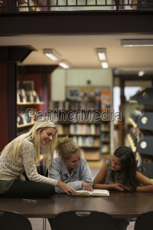 three female students in a library