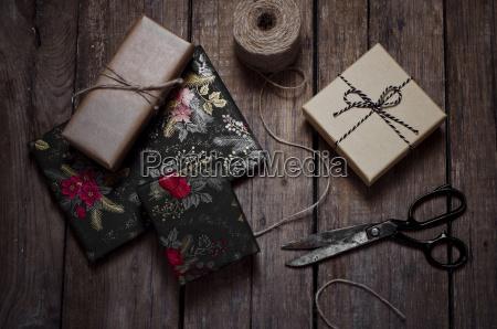 verpackte weihnachtsgeschenke schere und schnur auf