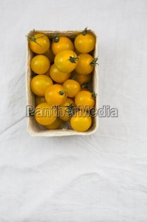 box of yellow cherry tomatoes on