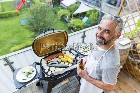 laechelnd mant grillen auf seinem balkon