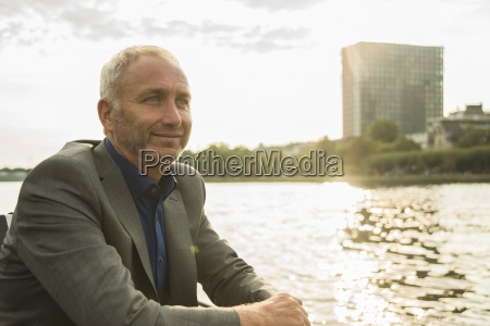 germany frankfurt relaxed businessman at river
