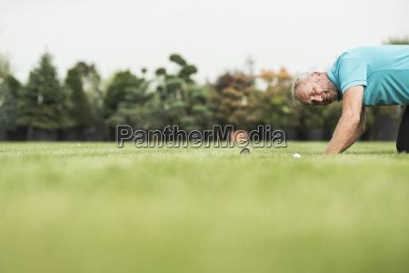 golf player kneeling on turf looking