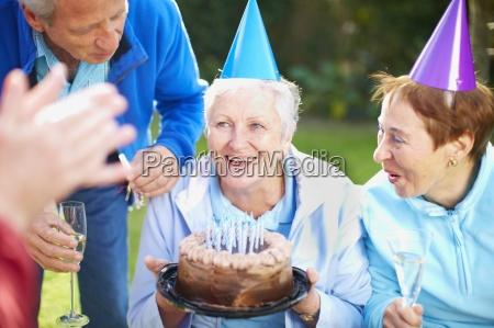 senior woman holding birthday cake on