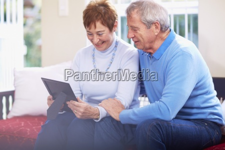 smiling senior couple looking at photo