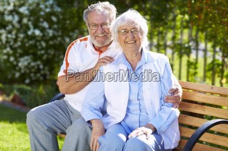 happy senior couple on park bench