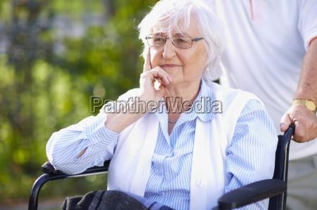 man pushing senior woman in wheelchair