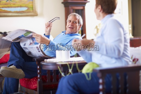 senior man with newspaper at home