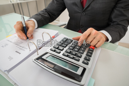 close up of businessman calculating invoice