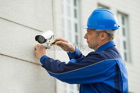 mature technician installing camera on wall