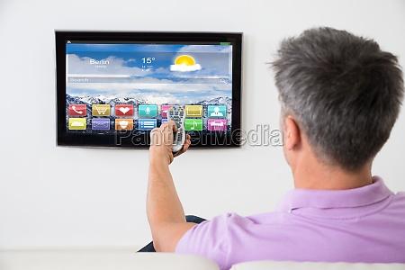 man on sofa using remote control