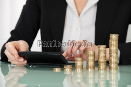 businesswoman using calculator with stacked coins