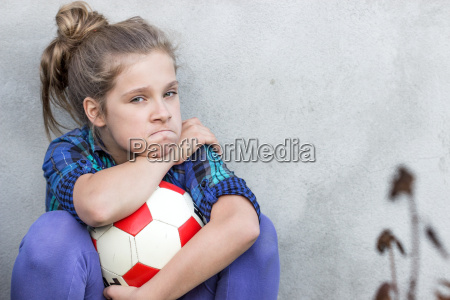 a young girl holds a ball