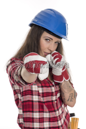 female artisan with construction helmet threatening