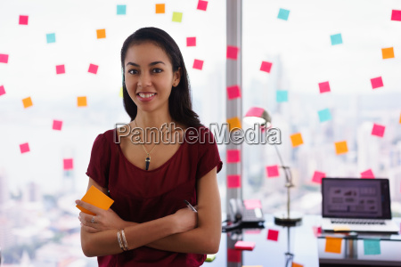 portrait business woman writing sticky notes