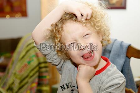 little blond boy making faces
