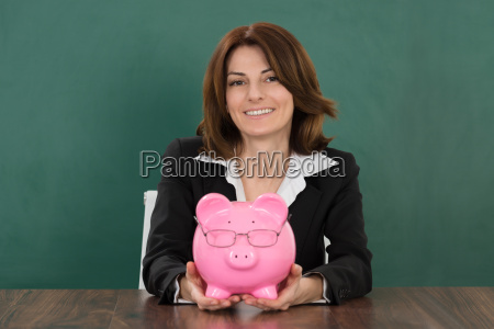 female teacher holding piggybank