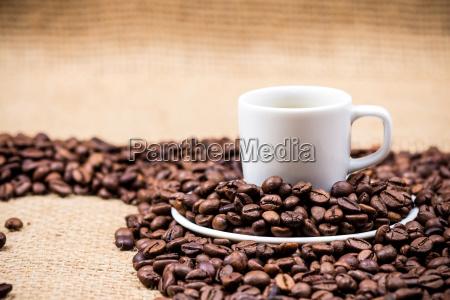 white coffeecup on coffeebeans