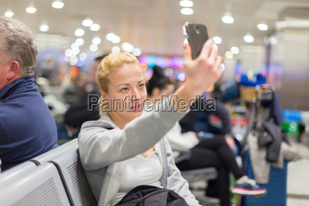 female traveler taking selfie on airport