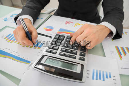 businessman analyzing graph and using calculator