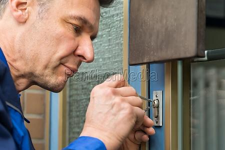male lockpicker fixing door handle at