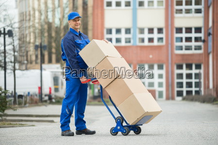 deliveryman holding trolley loaded with cardboard