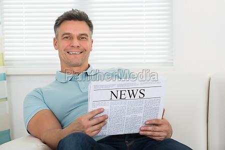 man reading newspaper sitting on sofa