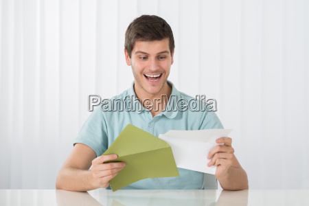 happy man holding letter on desk